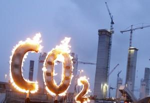 ARCHIV - Aktivisten der Umweltschutzorganisation Greenpeace stehen am 11.12.2008 in Hamburg neben einem brennenden «CO2»-Schriftzug an der Baustelle des Kohlekraftwerks in Hamburg-Moorburg. Der Ausstoß von klimaschädlichem Kohlendioxid ist in Hamburg leicht gestiegen. Foto: Marcus Brandt/dpa (zu dpa «Hamburg produziert mehr CO2 - Umweltschützer kritisieren Industrie» vom 09.03.2015)